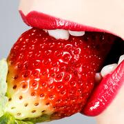 Beautiful juicy strawberry and female lips - stock photo