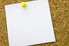 yellow postit on a everyday corkboard..this is my corkboard. - stock photo