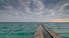 Alone concrete pier with clear ocean and stormy clouds Kuvituskuvat