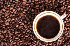 A cup of hot coffee on coffee beans background Stock Photos