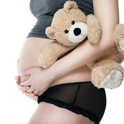 Belly of pregnant woman with a teddy bear hugged - stock photo