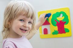 Happy girl playing soft constructor - stock photo