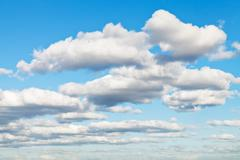 white and grey fluffy clouds in blue sky in spring - stock photo