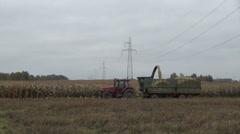 Harvester combine load ripe corn plants into tractor trailer Stock Footage