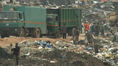 Waste lorries surrounded by men scavenging at dump Stock Footage