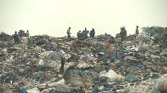 Steaming mountain of garbage with human scavengers Stock Footage