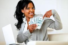 Happy woman pointing plenty of cash money - stock photo