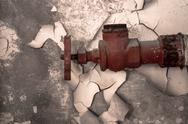 Stock Photo of Rusty old tap against concrete wall