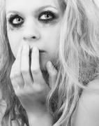 A sad blond girl with terrified expression - stock photo