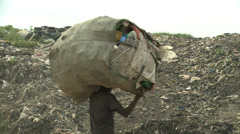 Man with huge bag of waste on head walks across dump Stock Footage