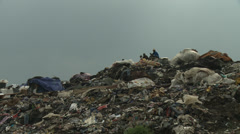 Steaming waste mountain with tiny human figures on top, truck thro' foreground Stock Footage