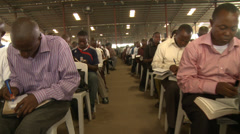 Men seated, Nigerian mega church, tracking shot Stock Footage