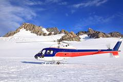 Helicopter landing on top of Franz Josef Glacier in New Zealand. Stock Photos