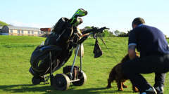 Golfer with his dog on the golf course Stock Footage