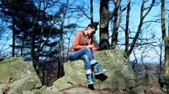 Woman texting on the cellphone and sitting on the rock in the mountainous area Stock Footage