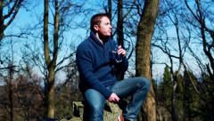 Man drinking water and sitting on a rock in the forest Stock Footage