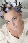 Portrait of sceptical looking bride with curlers - stock photo