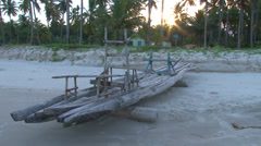 Slow zoom in of a jangada in the sunset among the coconut trees Stock Footage
