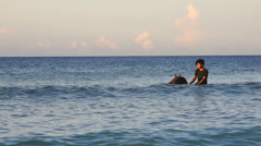 Local man with horse walks in the sea by sunset on the beach Stock Footage