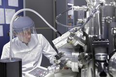 Stock Photo of Scientist sitting in analytical laboratory with scanning electron microscope and