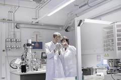 Stock Photo of Two scientists standing in analytical laboratory with scanning electron
