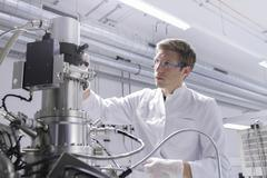 Stock Photo of Scientist standing in analytical laboratory with scanning electron microscope