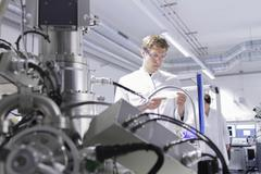 Stock Photo of Scientist standing in analytical laboratory with scanning electron microscope in