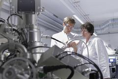 Two scientists standing in analytical laboratory with scanning electron Stock Photos