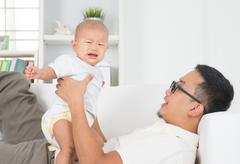 Father comforting crying baby. Stock Photos