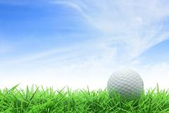 Stock Photo of golf ball on green grass against blue sky