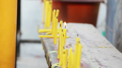 Row of candles in buddhistic temple outdoor Stock Footage