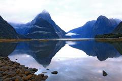 reflection of high mountain glacier at milford sound, New Zealan - stock photo
