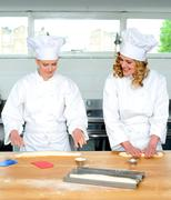 Senior chef teaching newbie female chef Stock Photos