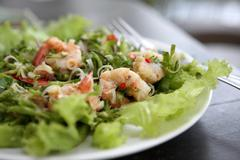 Thai dressed spicy salad with prawn and pork in wood background Stock Photos
