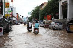 Chiangmai, thaimaa - syyskuu 28: ihmiset moottoripyörä ajaa läpi tulva Kuvituskuvat