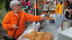 Woman serves waffles at stall Stock Footage