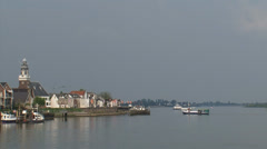 Skyline village at river Lek + ferry boat for pedestrians and bikers Stock Footage