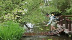 Asian man crossing footbridge getting feet wet Stock Footage