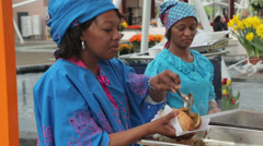 Surinam woman serving fast food in a bread roll Stock Footage