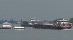 Rhine barges and container ship navigate Lek river + zoom out skyline village Stock Footage