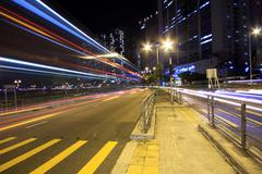 Blurred bus light trails in downtown night-scape. Stock Photos