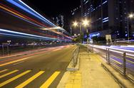 Stock Photo of blurred bus light trails in downtown night-scape.