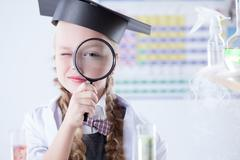 Smiling schoolgirl looks through magnifying glass - stock photo