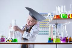 Educated girl following experimental results - stock photo