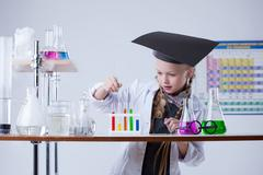 Image of smart little girl mixes reagents in lab Stock Photos