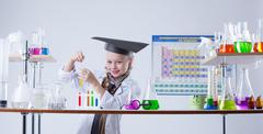 Adorable little chemist posing in lab with flasks - stock photo
