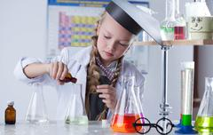 Adorable little girl conducting an experiment - stock photo