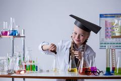 Smiling chemist mixes reagents in flask, close-up - stock photo
