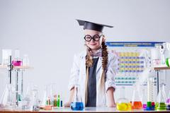Smiling little scientist posing in chemistry lab - stock photo