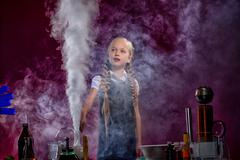 Charmed little girl pocing in cloud of steam - stock photo